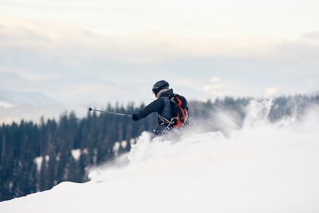 丘の中腹でスキーを降りる男性スキーヤーのバックパッカー