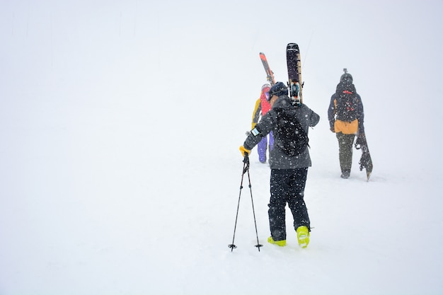 Male skier carries skis and equipment to the track on a slope of the mountain during snowfall on winter day