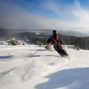 広く開いた山の斜面でフリーライディングする男性スキーヤー。モミの木の間をスキーで下ります。エクストリーム、アクティビティ、スリルのコンセプト。