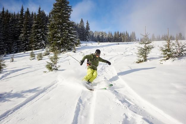 大きく開いたスキーでフリーライディングする男性スキーヤーは、下り坂を走ります。モミの木の間をスキーで下ります。極端な活動の概念