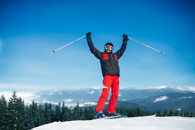 男性スキーヤーは山、青い空、森、雪に覆われた山の上に手を挙げます。冬のアクティブなスポーツ、極端なライフスタイル。ダウンヒルスキー