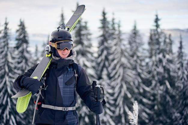 山でスキーをする前に、プロのスキー用具を肩に乗せて斜面の上に立っているゴーグルの男性スキーヤー。