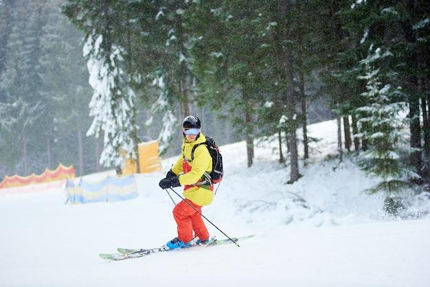 樹木が茂った斜面に立って、カメラでポーズをとって降雪の山のスキーで男性スキーヤー