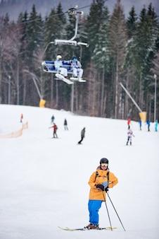 男性のスキーヤーがポーズをとり、スキーの上に立って、スキーストックに寄りかかっています。背景がぼやけている人。縦長のポートレートスナップショット