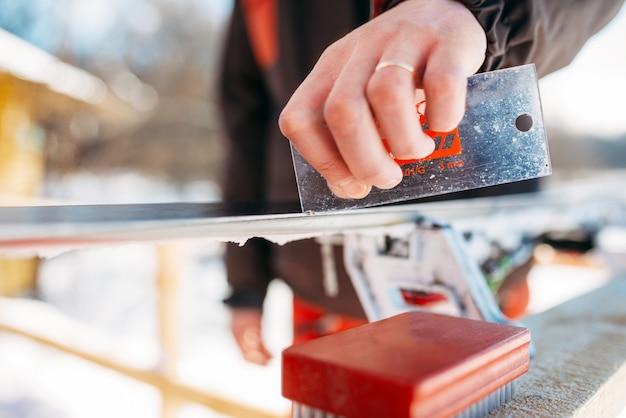 男性スキーヤーはスキー、クローズアップの前にスキーを提供しています。冬のアクティブなスポーツ、極端なライフスタイル。ダウンヒルスキー