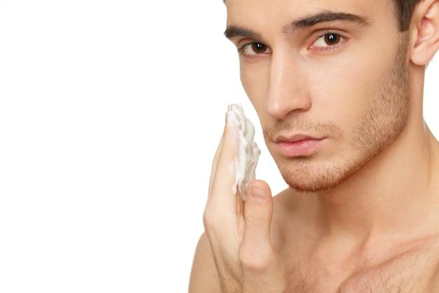 男性のスキンケア。側面の顔のコピースペースにシェービングクリームを塗っているハンサムな男性のスタジオショット