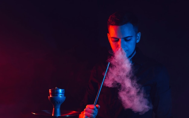 Male smoker smokes a hookah and lets out a cloud of smoke against the background of red and blue neon lights
