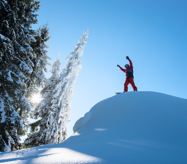 Male snowboarder freerider standing on top of the ski slope with his arms in the air in victorious gesture in the mountains