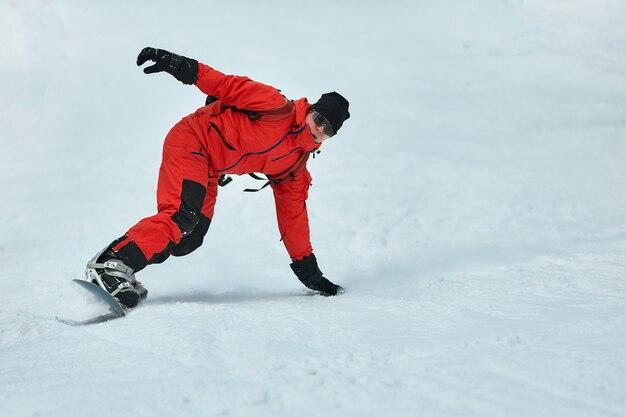 빨간 옷을 입은 남성 스노가 스노우 보드, 스키 및 스노우 보드 개념으로 눈 덮인 언덕에 타기