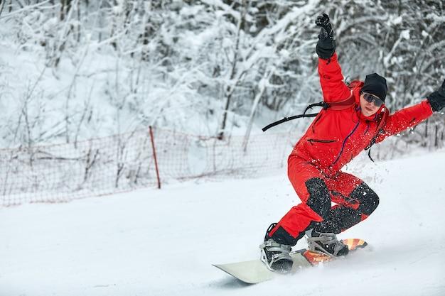 빨간 옷을 입은 남성 스노는 스노우 보드, 스키 및 스노우 보드 개념으로 눈 덮인 언덕에 탄다.
