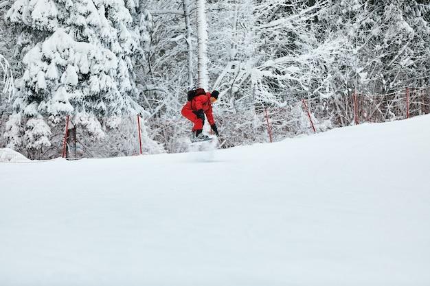 빨간 옷을 입은 남자 스노보더는 스노우보드, 스키, 스노우보드 컨셉으로 눈 덮인 언덕을 탄다.