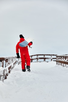 스노우 보드, 스키 및 스노우 보드 개념으로 눈 덮인 언덕을 걷고있는 빨간 옷의 남성 스노