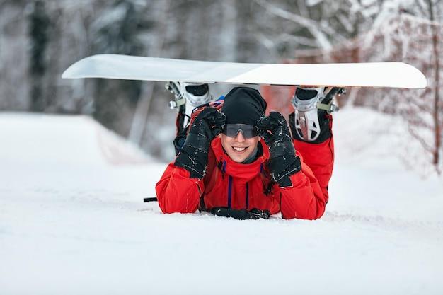 스노보드, 스키, 스노보드 컨셉으로 눈 덮인 언덕을 걷고 있는 빨간 옷을 입은 남성 스노보더.