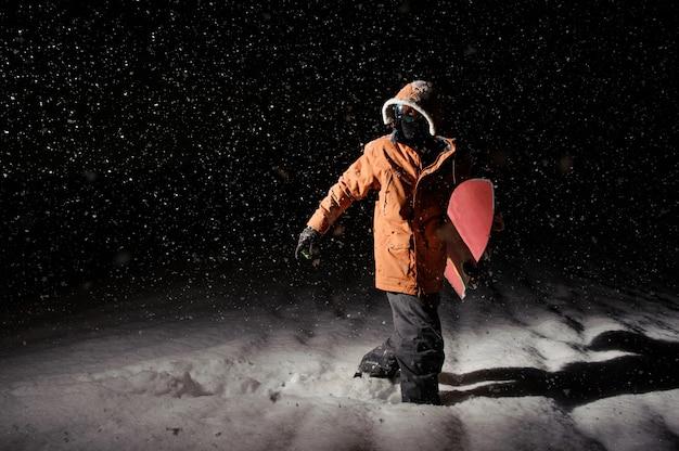 Мужской сноубордист в оранжевой спортивной куртке гуляет по снегу с доской в руке