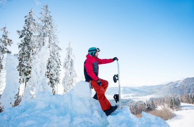 Мужской сноубордист отдыхает на вершине склона