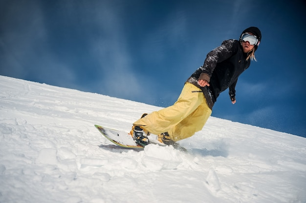 Male snowboarder riding down the mountain slope