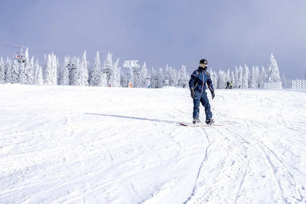 Male snowboarder riding down the slope with a beautiful winter landscape in the background