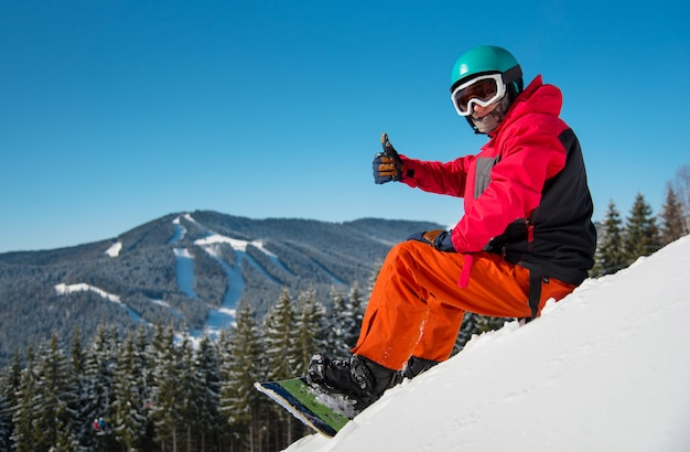 Male snowboarder sitting, relaxing on the snowy slope at winter ski resort in the mountains, showing thumbs up to the camera