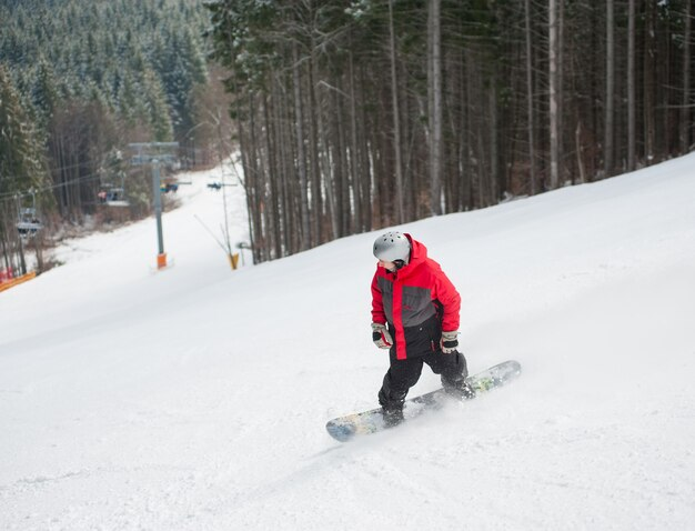 Male snowboarder slides down from the mountain in winter day, overlooking the snowy slope and forest at a winter resort