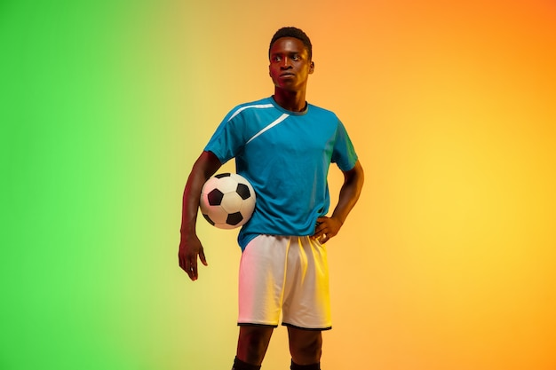 Male soccer, football player training in action isolated on gradient studio in neon light