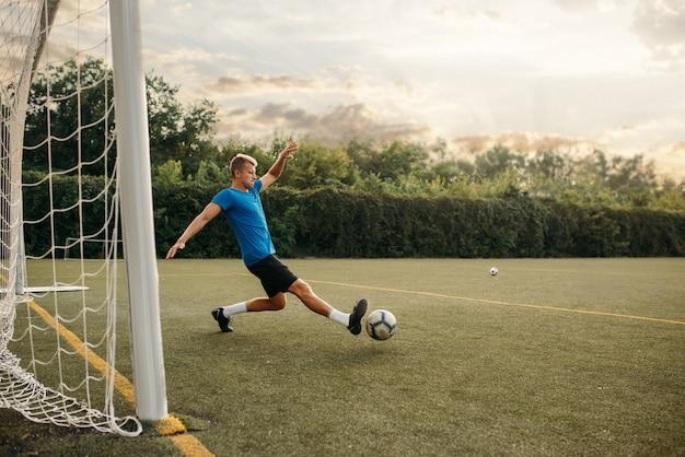 Мужской вратарь футбола бьет по мячу и спасает ворота. футболист на открытом стадионе, тренировка перед игрой, футбольная тренировка