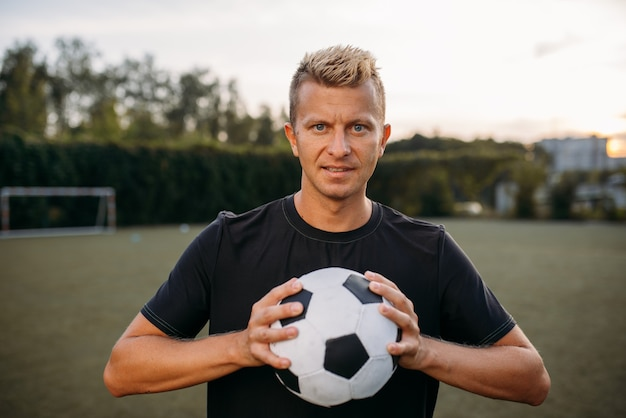 Male soccer player holding ball in hands on the field. footballer on outdoor stadium, workout before game, football training