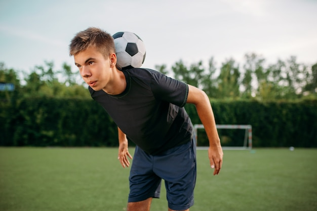 남자 축구 선수는 필드에서 그의 목에 공과 균형을 유지합니다. 야외 경기장에 축구 선수, 경기 전 팀 운동