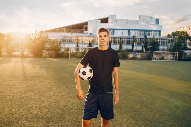남자 축구 선수는 해돋이에 분야에 손에 공을 포즈. 야외 경기장의 축구 선수, 경기 전 운동, 축구 훈련
