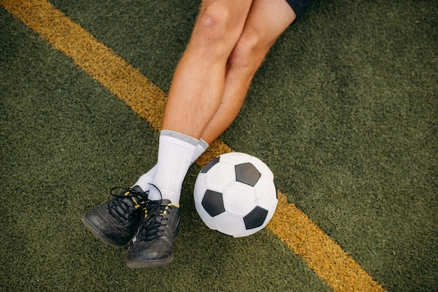 Male soccer player with ball sitting on the grass on the field. footballer on outdoor stadium, workout before game, football training