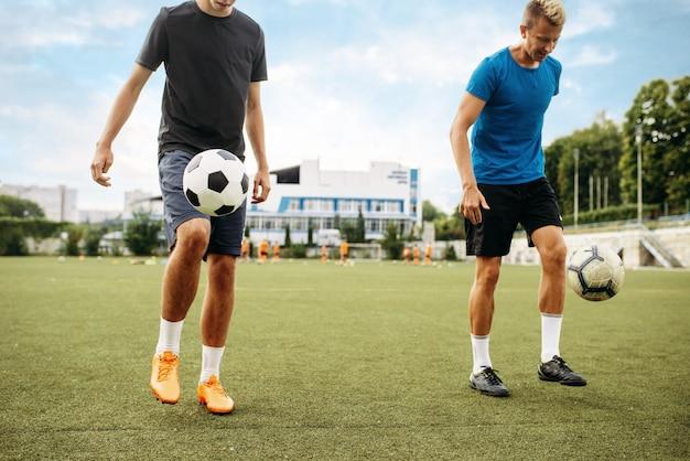 남자 축구 선수는 필드에 발로 공을 채운다. 야외 경기장에 축구 선수, 경기 전 팀 운동