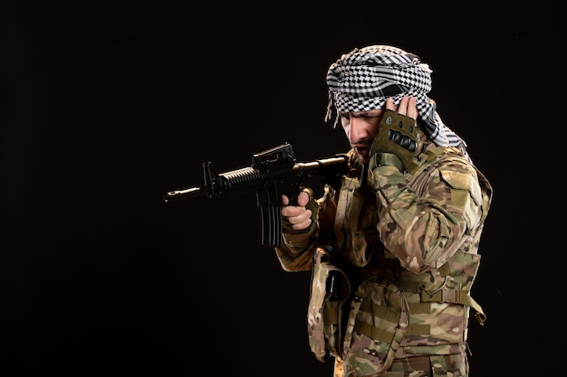 Male soldier in camouflage aiming machine gun on black wall