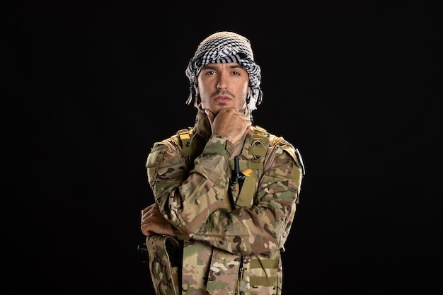 Male soldier in camouflage on black wall