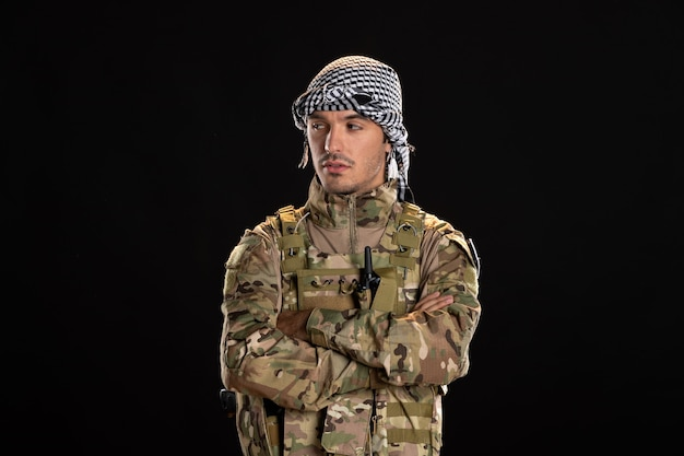 Male soldier in camouflage on the black wall