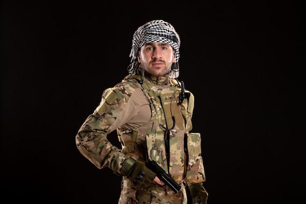 Soldato maschio in mimetica che combatte con la pistola sul muro nero