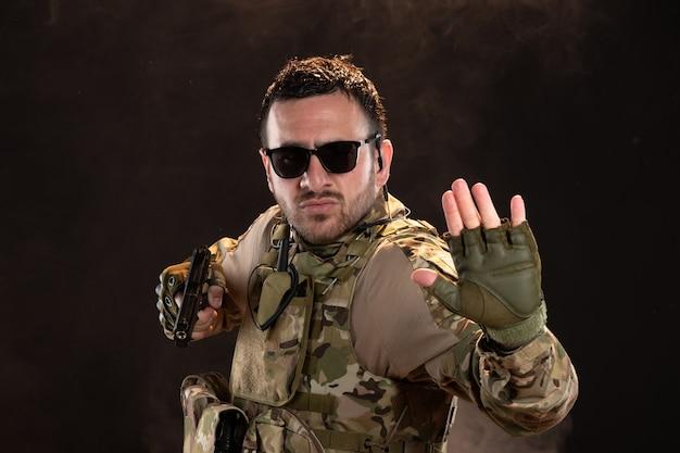 Soldato maschio in mimetica che combatte con la pistola sul muro scuro