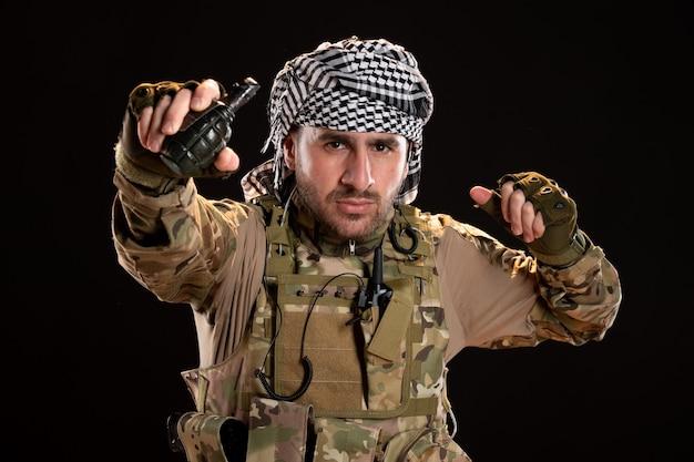 Soldato maschio in mimetica che tiene una granata sul muro nero