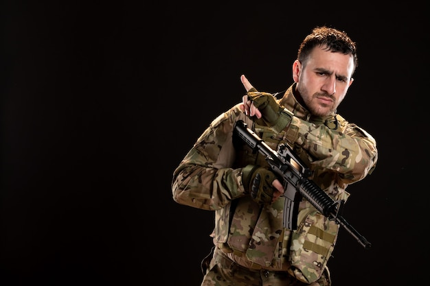 Male soldier in camouflage holding machine gun on black wall