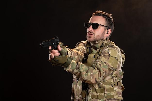Soldato maschio in mimetica con pistola sul muro nero