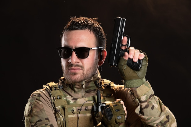 Male soldier in camouflage with gun on black wall