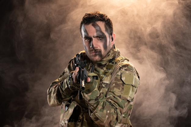 Male soldier in camouflage with machine gun on dark wall
