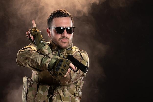 어두운 벽에 총을 목표로 위장에 남성 군인
