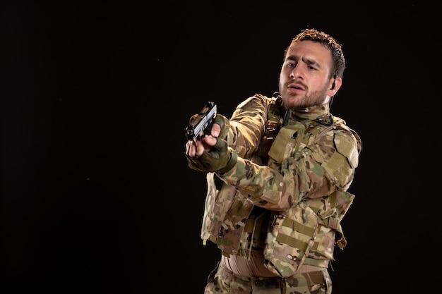 검은 벽에 총을 목표로 위장에 남성 군인