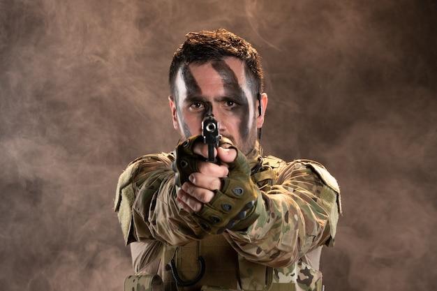연기가 자욱한 어두운 벽에 총을 목표로 위장에 남성 군인