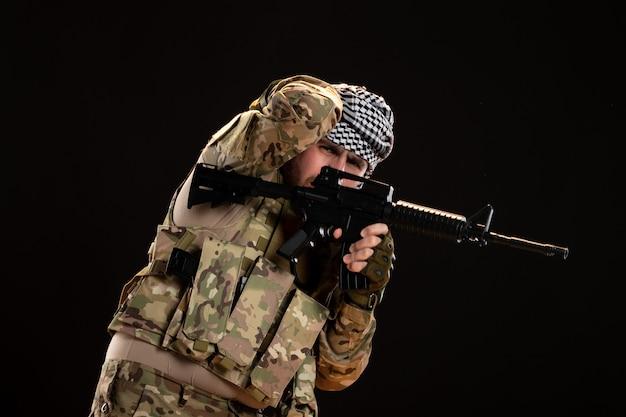 검은 벽에 기관총과 싸우는 위장에 남성 군인