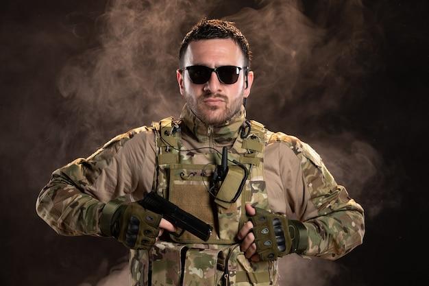 어두운 벽에 총을 들고 위장에 남성 군인