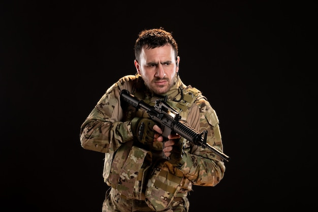 검은 벽에 기관총을 들고 위장에 남성 군인