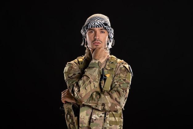 黒い壁に迷彩を着た男性兵士