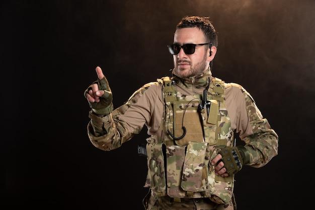 Мужчина-солдат в камуфляже на темной стене