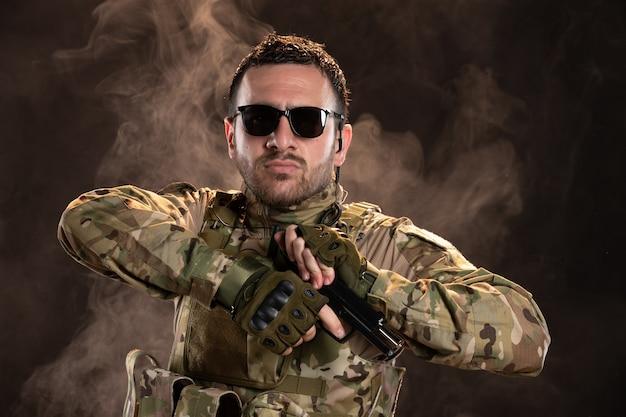어두운 벽에 총을 다시 장전하는 위장에 남성 군인