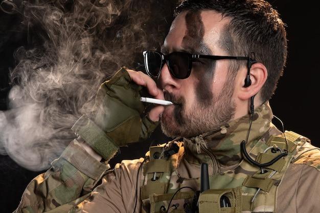 黒い壁にタバコを吸う迷彩の男性兵士
